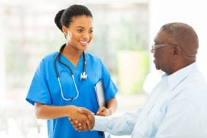 A nurse with a stethoscope smiles at a patient and shakes his hand